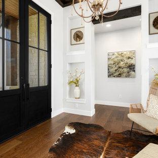 Immagine di un ingresso country di medie dimensioni con pareti bianche, parquet scuro, una porta a due ante, una porta nera, pavimento marrone e travi a vista