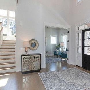 Exempel på en stor lantlig foajé, med vita väggar, ljust trägolv, en svart dörr och brunt golv