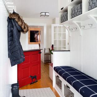 Bild på ett litet lantligt kapprum, med vita väggar, mellanmörkt trägolv, en tvådelad stalldörr och en röd dörr