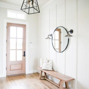 Modelo de distribuidor de estilo de casa de campo, de tamaño medio, con paredes blancas, suelo de madera clara, puerta simple, puerta de vidrio y suelo beige