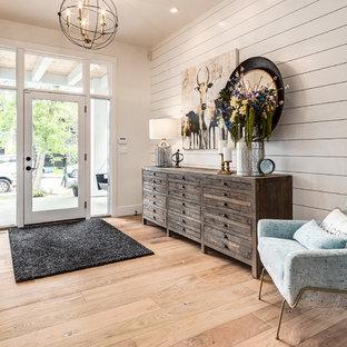 Modelo de distribuidor campestre, grande, con paredes blancas, suelo de madera clara, puerta simple, suelo beige y puerta de vidrio
