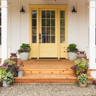 Réalisation d'une grand porte d'entrée champêtre avec un mur blanc, un sol en bois brun, une porte simple, une porte jaune et un sol marron.