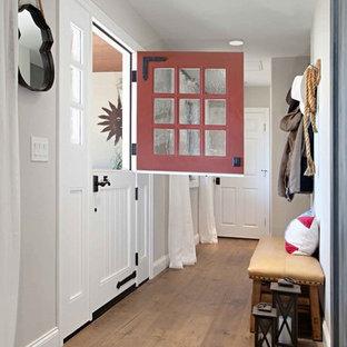 На фото: прихожая в стиле кантри с серыми стенами, темным паркетным полом, голландской входной дверью и красной входной дверью с