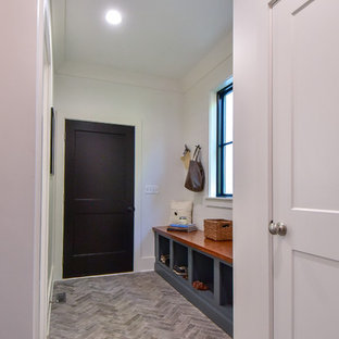 Small farmhouse porcelain tile and gray floor entryway photo in Other with white walls and a black front door