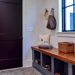 Entryway - small country porcelain floor and gray floor entryway idea in Other with white walls and a black front door