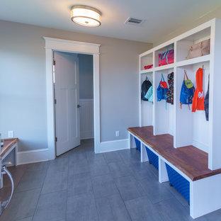 Aménagement d'une entrée campagne de taille moyenne avec un vestiaire, un mur gris, un sol en carrelage de céramique, une porte simple, une porte en bois brun et un sol gris.