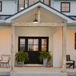 Diseño de puerta principal de estilo de casa de campo, de tamaño medio, con puerta negra, paredes blancas, suelo de cemento, puerta simple y suelo gris