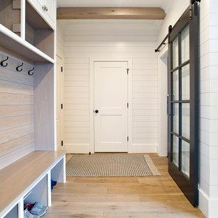 Foto på ett lantligt kapprum, med vita väggar, ljust trägolv och brunt golv