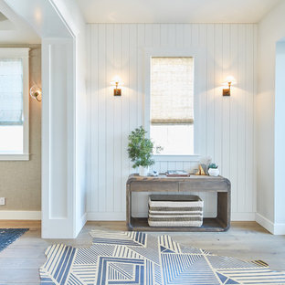Inspiration for a beach style light wood floor and beige floor entryway remodel in Los Angeles with white walls and a white front door