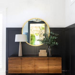Ispirazione per un ingresso country con pareti nere, parquet chiaro, una porta singola e una porta nera