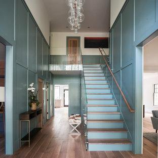 Landhaus Eingang mit Foyer, grüner Wandfarbe, braunem Holzboden und braunem Boden in New York