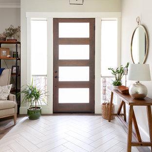 Cette photo montre un hall d'entrée moderne de taille moyenne avec un mur gris, une porte simple, une porte en bois foncé, un sol en bois brun et un sol marron.
