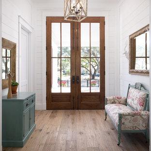 Bild på en lantlig hall, med vita väggar, ljust trägolv, en dubbeldörr, mörk trädörr och beiget golv