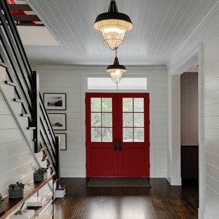 Exempel på en stor lantlig foajé, med vita väggar, mörkt trägolv, en dubbeldörr, en röd dörr och brunt golv
