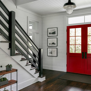 Entryway - large farmhouse dark wood floor and brown floor entryway idea in New York with white walls and a red front door