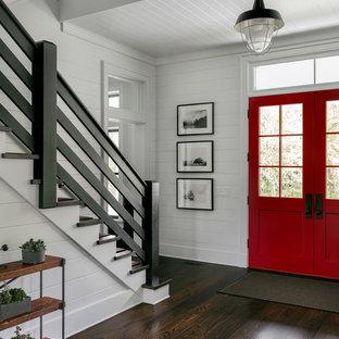 Ejemplo de distribuidor de estilo de casa de campo, grande, con paredes blancas, suelo de madera oscura, puerta doble, puerta roja y suelo marrón
