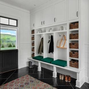 Modelo de vestíbulo posterior de estilo de casa de campo, grande, con paredes blancas, puerta tipo holandesa, puerta negra y suelo negro