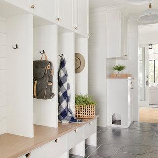 Inspiration för lantliga kapprum, med vita väggar och svart golv