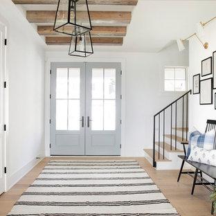 Bild på en lantlig foajé, med vita väggar, ljust trägolv, en dubbeldörr och glasdörr