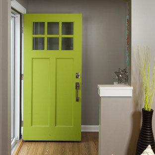Foto di un ingresso tradizionale di medie dimensioni con pareti grigie, pavimento in legno massello medio, una porta singola e una porta verde