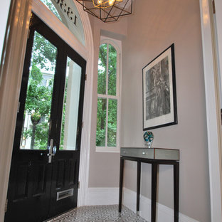 Example of a small transitional marble floor and brown floor entryway design in DC Metro with beige walls and a black front door