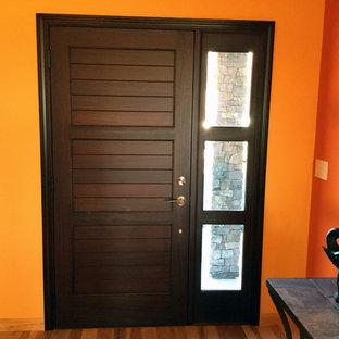 Imagen de puerta principal actual con parades naranjas, suelo de madera en tonos medios, puerta simple y puerta de madera oscura