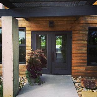 Diseño de puerta principal minimalista, de tamaño medio, con paredes marrones, puerta negra, suelo gris y puerta doble