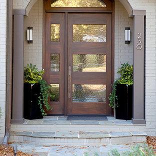 Imagen de entrada clásica renovada con paredes beige, suelo de pizarra, puerta simple y puerta de madera en tonos medios