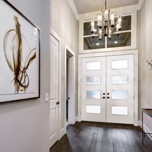 Идея дизайна: большое фойе в стиле модернизм с бежевыми стенами, темным паркетным полом, двустворчатой входной дверью, белой входной дверью, коричневым полом и сводчатым потолком