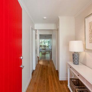 Modelo de hall costero, de tamaño medio, con paredes blancas, suelo de madera en tonos medios, puerta simple y puerta roja
