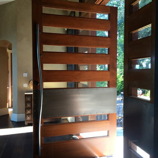 Inspiration for a huge industrial dark wood floor entryway remodel in Portland with a medium wood front door and beige walls