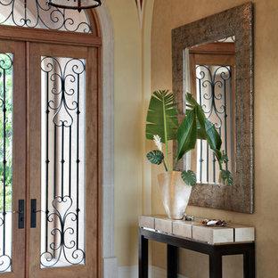 Entryway - mid-sized mediterranean beige floor entryway idea in Miami with beige walls and a glass front door