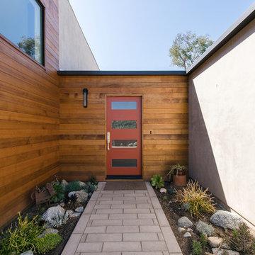 modern red entry door at cedar siding