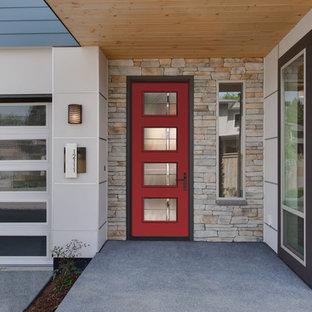 Immagine di un ingresso o corridoio minimalista con pavimento in cemento, una porta singola e una porta rossa