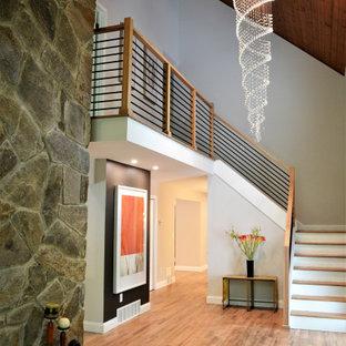 На фото: большое фойе в стиле ретро с серыми стенами, светлым паркетным полом, одностворчатой входной дверью, входной дверью из темного дерева и деревянным потолком с