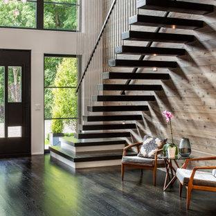 Ejemplo de entrada madera, contemporánea, con paredes marrones, suelo de madera oscura, puerta simple, puerta de vidrio, suelo marrón y madera