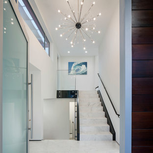 Entryway - contemporary marble floor entryway idea in San Diego with white walls and a glass front door