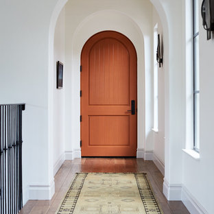 Inspiration for a mid-sized mediterranean medium tone wood floor and brown floor entryway remodel in San Francisco with white walls and an orange front door