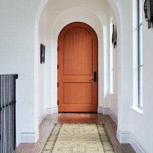 Medelhavsstil inredning av en mellanstor ingång och ytterdörr, med vita väggar, mellanmörkt trägolv, en enkeldörr, en orange dörr och brunt golv