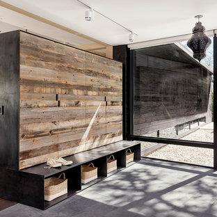 オースティンの広い片開きドアモダンスタイルのおしゃれなマッドルーム (濃色木目調のドア、黒い壁) の写真