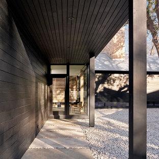 Idee per un ingresso con anticamera minimalista con pareti nere, una porta singola e una porta nera