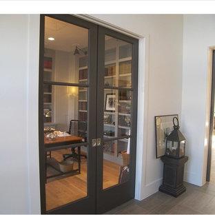 Immagine di un ingresso minimalista con pareti bianche, una porta nera, parquet chiaro e una porta scorrevole