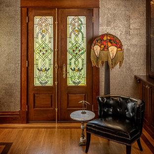 Esempio di un ingresso o corridoio chic di medie dimensioni con pavimento in legno massello medio, pavimento marrone, pareti grigie, una porta a due ante e una porta in legno bruno