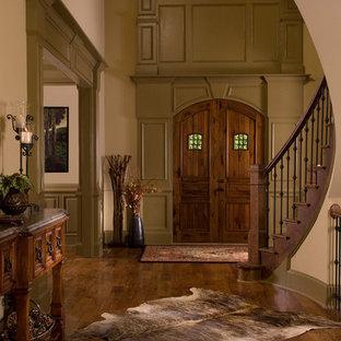 Idee per un ingresso o corridoio stile rurale con una porta a due ante, una porta in legno scuro e pavimento marrone