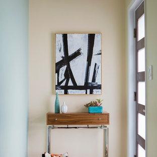 Modern inredning av en liten foajé, med blå väggar, en enkeldörr, glasdörr, bambugolv och brunt golv