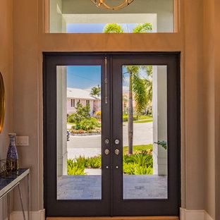 Exemple d'un hall d'entrée chic de taille moyenne avec un mur beige, un sol en bois clair, une porte double, une porte en verre et un sol marron.