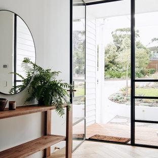 メルボルンの広い片開きドアコンテンポラリースタイルのおしゃれな玄関ロビー (白い壁、淡色無垢フローリング、黒いドア、黒い床、パネル壁) の写真