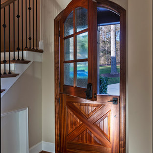 Example of a mountain style medium tone wood floor and brown floor entryway design in Charlotte with a medium wood front door