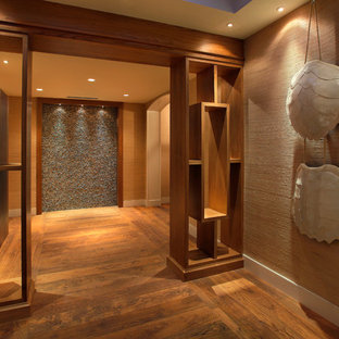 Example of a trendy medium tone wood floor foyer design in Miami with beige walls