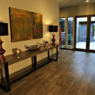 Idee per una grande porta d'ingresso minimal con pareti beige, parquet scuro, una porta a due ante, una porta in vetro e pavimento marrone